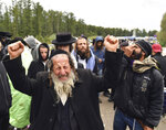 A Hasidic Jewish pilgrim reacts as he joins others, in front of Ukrainian border guards at the checkpoint Novaya Guta near Novaya Guta, Belarus, Friday, Sept. 18, 2020. Ukrainian officials say that thousands of Hasidic Jewish pilgrims stuck on the Ukrainian border due to coronavirus restrictions have started turning back. About 2,000 ultra-Orthodox Jewish pilgrims traveled to Belarus's border with Ukraine in hope of traveling to the Ukrainian city of Uman to visit the grave of an important Hasidic rabbi who died in 1810, Nachman of Breslov. (AP Photo)