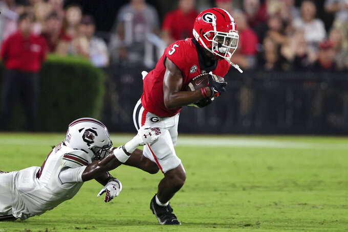 Georgia wide receiver Adonai Mitchell (5) breaks free from the arms of South Carolina defensive back Cam Smith (9) after catching a pass during the first half of an NCAA college football game Saturday, Sept. 18, 2021, in Athens, Ga. (AP Photo/Butch Dill)