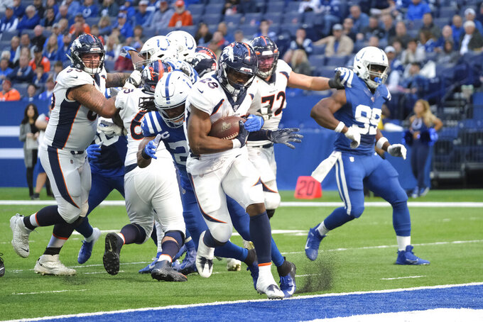 Denver Broncos' Royce Freeman (28) goes in for a touchdown while being tackled by dIndianapolis Colts' Clayton Geathers (26) during the second half of an NFL football game, Sunday, Oct. 27, 2019, in Indianapolis. (AP Photo/AJ Mast)