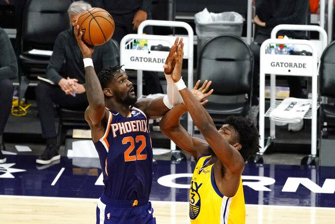 Phoenix Suns center Deandre Ayton (22) shoots over Golden State Warriors center James Wiseman during the second half of an NBA basketball game Thursday, March 4, 2021, in Phoenix. (AP Photo/Rick Scuteri)