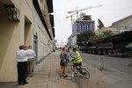 Passers-by watch and take pictures near the Hard Rock Hotel, Thursday, Oct. 17, 2019, in New Orleans.  The 18-story hotel project that was under construction collapsed last Saturday, killing three workers. Two bodies remain in the wreckage. (AP Photo/Gerald Herbert)