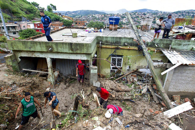 Locals work to clean up mud and debris around houses destroyed by a landslide after heavy rains in Vila Ideal neighborhood, Ibirite municipality, Minas Gerias state, Brazil, Saturday, Jan.25, 2020. Heavy rains caused flooding and landslides in southeast Brazil, killing at least 30 people, authorities said Saturday. (AP Photo/Alexandre Mota-Futura Press)