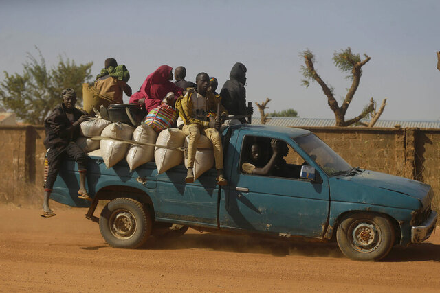 People travel past Government Science Secondary School in Kankara, Nigeria, Tuesday, Dec. 15, 2020. Rebels from the Boko Haram extremist group claimed responsibility Tuesday for abducting hundreds of boys from the school in Nigeria's northern Katsina State last week in one of the largest such attacks in years, raising fears of a growing wave of violence in the region. (AP Photo/Sunday Alamba)