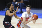 Florida forward Colin Castleton (12) looks to pass the ball around South Carolina forward Justin Minaya (10) during the first half of an NCAA college basketball game Wednesday, Feb. 3, 2021, in Gainesville, Fla. (AP Photo/Matt Stamey)