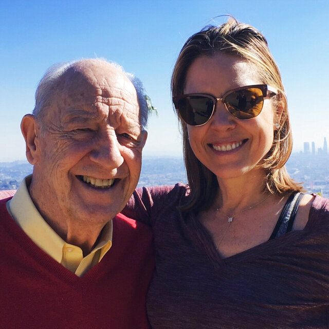 In a photo provided by Hannah Storm, Hannah Storm poses for a photo with her father, Mike Storen, in Los Angeles on Dec. 29, 2015. Storen, a former ABA commissioner and multisport marketing whiz and the father of ESPN broadcaster Hannah Storm, died Thursday, May 7, 2020. He was 84. Storm said her father died at Emory University Hospital in Atlanta of complications from cancer. (Hannah Storm via AP)
