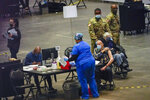 Seniors are vaccinated against COVID-19 at a New York State vaccination site in the Jacob K. Javits Convention Center, Wednesday, Jan. 13, 2021, in New York. New York state expanded COVID-19 vaccine distribution Tuesday to people 65 and over, increasing access to an already short supply of doses being distributed. (AP Photo/Mary Altaffer)