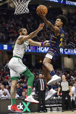 Cleveland Cavaliers' Collin Sexton, right, drives to the basket against Boston Celtics' Jayson Tatum in the second half of an NBA basketball game, Wednesday, March 4, 2020, in Cleveland. Boston won 112-106. (AP Photo/Tony Dejak)