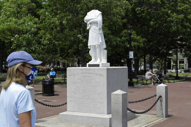 A passer-by walks near a damaged Christopher Columbus statue, Wednesday, June 10, 2020, in a waterfront park near the city's traditionally Italian North End neighborhood, in Boston. The statue was found beheaded Wednesday morning, Boston Mayor Marty Walsh said.  (AP Photo/Steven Senne)
