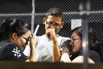 Three Walmart workers, Melisa Gonzalez, Jesus Romero and Raven Ramos, who helped people to escape during the mass shooting on Saturday, Aug. 3, 2019, get emotional during during a vigil at Ponder Park in honor of the shooting  victims in El Paso, Texas on Sunday, Aug. 4, 2019. (Lola Gomez/Austin American-Statesman via AP)