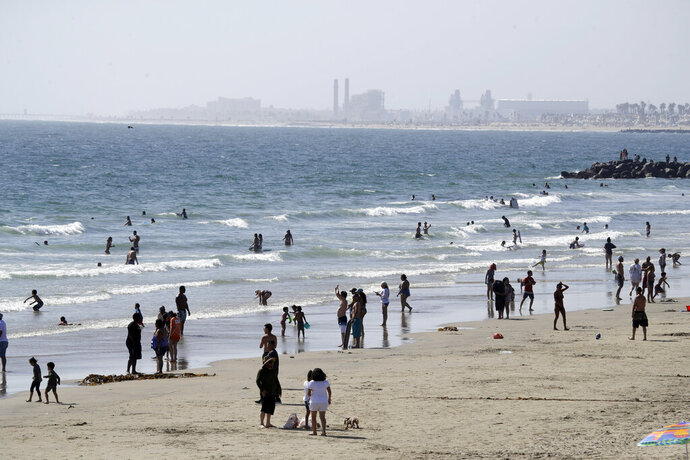 FILE - In this May 24, 2020 file photo, people visit the beach in Newport Beach, Calif., during the coronavirus pandemic. California Gov. Gavin Newsom said Wednesday, June 23, 2020, that he will leverage $2.5 billion in the upcoming state budget to penalize counties that fail to comply with the state's mandates on wearing masks, testing and other measures meant to slow the spread of the coronavirus. (AP Photo/Marcio Jose Sanchez, File)