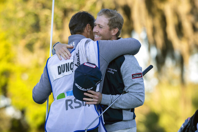 Tyler Duncan, right, hugs his caddie Zach Guthrie, left, after winning a second-hole playoff against Webb Simpson during the final round of the RSM Classic golf tournament in St. Simons Island, Ga., Sunday, Nov. 24, 2019. (AP Photo/Stephen B. Morton)