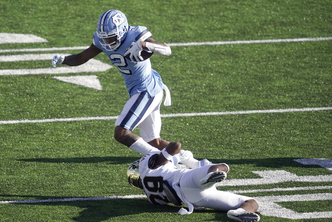 North Carolina wide receiver Dyami Brown (2) steps over Wake Forest defensive back Caelen Carson (29) during the second half of an NCAA college football game in Chapel Hill, N.C., Saturday, Nov. 14, 2020. (AP Photo/Gerry Broome)