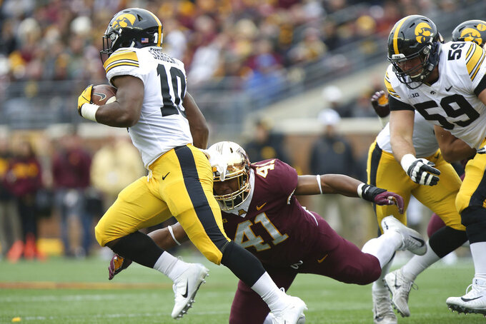 Iowa running back Mekhi Sargent escapes the tackle by Minnesota's Thomas Barber during an NCAA college football game Saturday, Oct. 6, 2018, in Minneapolis. (AP Photo/Stacy Bengs)