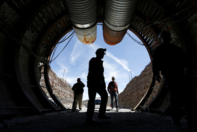 FILE - In this April 9, 2015, file photo, people walk into the south portal of Yucca Mountain during a congressional tour of the proposed radioactive waste dump near Mercury, Nev., 90 miles northwest of Las Vegas. A federal judge in Reno has agreed to allow Nevada to amend its lawsuit in an ongoing legal battle with the U.S. Energy Department to try to show why the government should be forced to remove weapons-grade plutonium it secretly shipped to a site near Las Vegas last year over the state's objections. (AP Photo/John Locher, File)