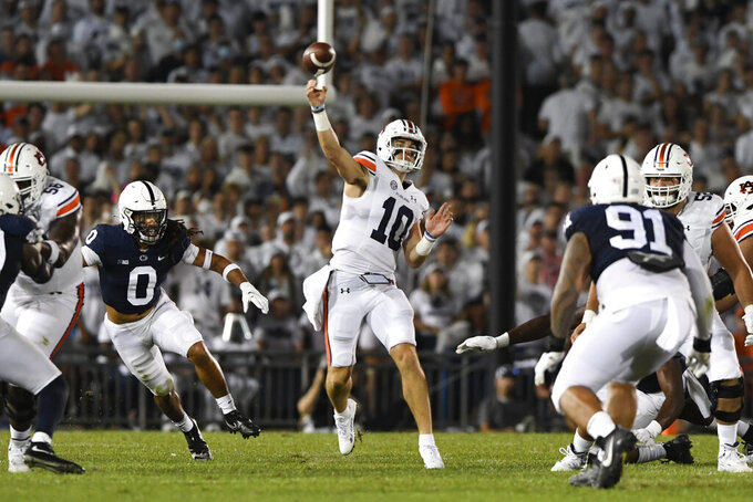 Auburn quarterback Bo Nix (10) passes while being pressured by Penn State safety Jonathan Sutherland (0) during an NCAA college football game in State College, Pa., on Saturday, Sept. 18, 2021. (AP Photo/Barry Reeger)