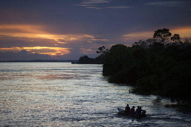 FILE - In this May 22, 2014 file photo, a small boat navigates on the Solimoes River near Manaus, Brazil. In the remote Amazon community of Betania, indigenous Tikuna tribe members suspect the new coronavirus arrived in May of 2020 after some returned from a two-hour boat trip down the Solimoes River to pick up their government benefit payments. (AP Photo/Felipe Dana, File)