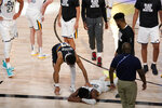 Denver Nuggets' Jamal Murray, center left, reaches down to console Utah Jazz's Donovan Mitchell (45), on floor, after the Nuggets 80-78 win during an NBA first round playoff basketball game, Tuesday, Sept. 1,2020, in Lake Buena Vista, Fla. (AP Photo/Mark J. Terrill)