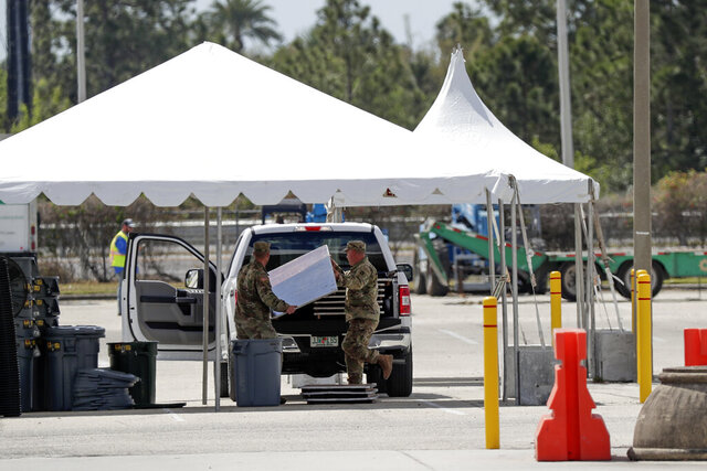 Military personnel move equipment as they set up a virus testing facility at the Orange County Convention Center Friday, March 20, 2020, in Orlando, Fla. Testing will begin Monday at the center. (AP Photo/John Raoux)