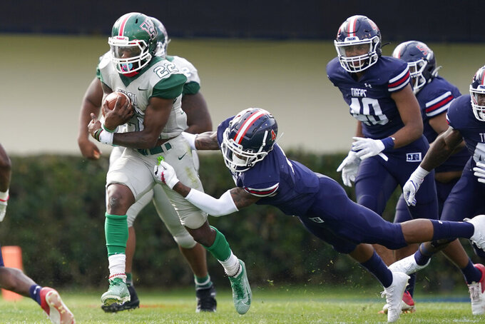 A Jackson State defender attempts to tackle Mississippi Valley State running back Dederrian Williams (22) during the second half of an NCAA college football game, Sunday, March 14, 2021, in Jackson, Miss. (AP Photo/Rogelio V. Solis)