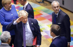 British Prime Minister Boris Johnson, center, salutes French President Emmanuel Macron, second right, during a round table meeting at an EU summit in Brussels, Thursday, Oct. 17, 2019. Britain and the European Union reached a new tentative Brexit deal on Thursday, hoping to finally escape the acrimony, divisions and frustration of their three-year divorce battle. (AP Photo/Olivier Matthys, Pool)