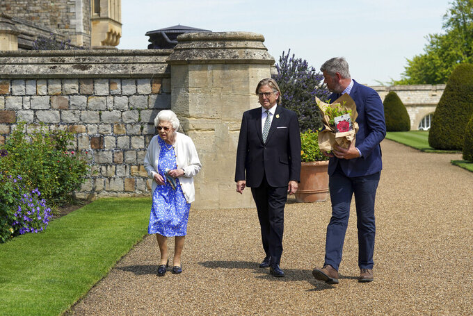Britain's Queen Elizabeth II looks at flower beds after receiving a Duke of Edinburgh rose, given to her by Keith Weed, centre, President of the Royal Horticultural Society, at Windsor Castle, England, Wednesday June 9, 2021. The newly bred deep pink commemorative rose has officially been named in memory of the late Prince Philip Duke of Edinburgh. A royalty from the sale of each rose will go to The Duke of Edinburgh's Award Living Legacy Fund to support young people taking part in the Duke of Edinburgh Award scheme.  (Steve Parsons/Pool via AP)