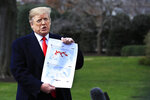 President Donald Trump shows a map of Syria and Iraq showing the presence of the Islamic State (IS) in 2017 and 2019, as he speaks to reporters before leaving the White House in Washington, Wednesday, March 20, 2019, for a trip to visit a Army tank plant in Lima, Ohio, and a fundraising event in Canton, Ohio. (AP Photo/Manuel Balce Ceneta)