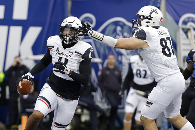 Cincinnati tight end Leonard Taylor (11) is congratulated by tight end Bruno Labelle (87) after scoring a touchdown against Memphis in the first half of an NCAA college football game Friday, Nov. 29, 2019, in Memphis, Tenn. (AP Photo/Mark Humphrey)