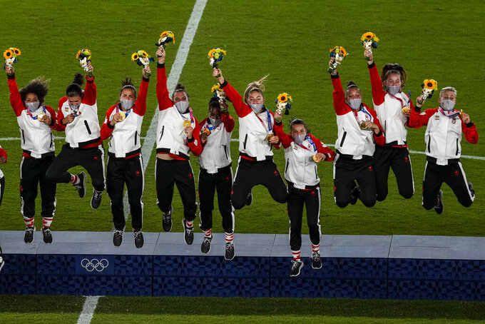 Canada national soccer team members celebrate after winning the women's final gold medal at the 2020 Summer Olympics, Friday, Aug. 6, 2021, in Yokohama, Japan. (AP Photo/Kiichiro Sato)