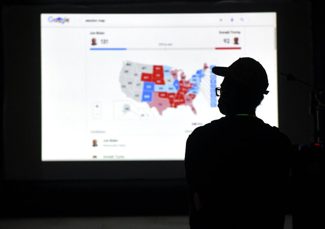 A man watches results come in on a screen set up at an election night gathering at Independence Mall , Tuesday, Nov. 3, 2020, in Philadelphia. (AP Photo/Michael Perez)