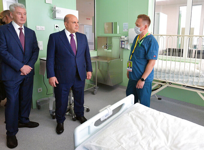 FILE - In this Friday, June 18, 2021, file photo, Russian Prime Minister Mikhail Mishustin, center, and Moscow's Mayor Sergei Sobyanin, left, visit the hospital for coronavirus patients in Kommunarka, outside Moscow, Russia. An ambitious plan of vaccinating 30 million Russians by mid-June against the coronavirus has fallen short by a third, and the country has started to see a surge in daily new infections. So now, many regional governments across the vast country are obligating some workers to get vaccinated and requiring the shots to enter certain businesses, like restaurants. (Alexander Astafyev, Sputnik/Kremlin Pool Photo via AP, File)
