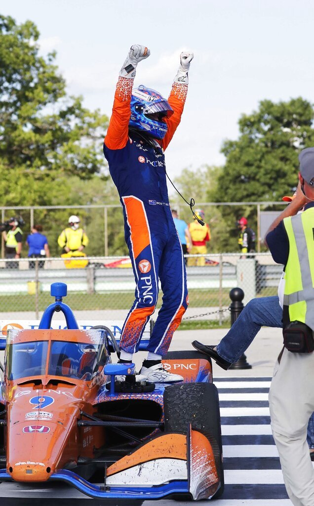 IndyCar driverScott Dixon (9) raises his arms to celebrate his win in the REV Group Grand Prix auto race one, Saturday, July 11, 2020, in Elkhart Lake, Wis. (Gary C. Klein/The Sheboygan Press via AP)