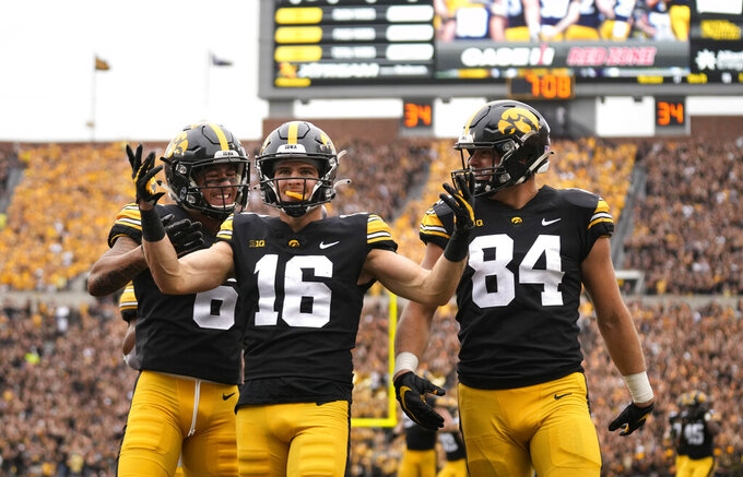 Iowa wide receiver Charlie Jones (16) celebrates his touchdown with receiver Keagan Johnson (6) and tight end Sam LaPorta (84) during the first half of an NCAA college football game against Penn State, Saturday, Oct. 9, 2021, in Iowa City, Iowa. (AP Photo/Matthew Putney)
