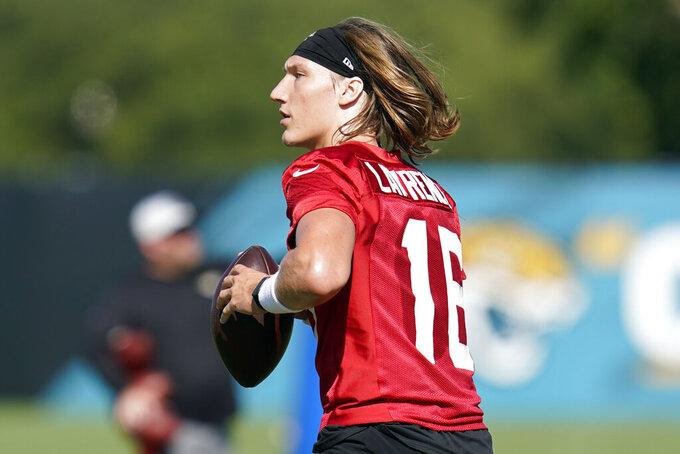 Jacksonville Jaguars quarterback Trevor Lawrence performs a drill during NFL football practice, Saturday, July 31, 2021, in Jacksonville, Fla. (AP Photo/John Raoux)
