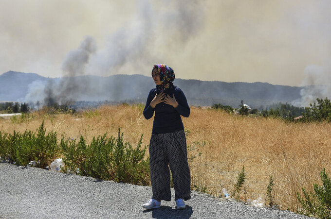 A woman looks at the wildfires in Kacarlar village near the Mediterranean coastal town of Manavgat, Antalya, Turkey, Saturday, July 31, 2021. The death toll from wildfires raging in Turkey's Mediterranean towns rose to six Saturday after two forest workers were killed, the country's health minister said. Fires across Turkey since Wednesday burned down forests, encroaching on villages and tourist destinations and forcing people to evacuate.(AP Photo)