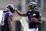 Baltimore Ravens quarterback Lamar Jackson, right, adjusts the helmet of running back Mark Ingram II during an NFL football camp practice, Monday, Aug. 17, 2020, in Owings Mills, Md. (AP Photo/Julio Cortez)