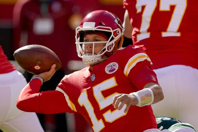 Kansas City Chiefs quarterback Patrick Mahomes (15) attempts to throw a pass as he is wrapped up by New York Jets' Quinnen Williams, bottom, in the first half of an NFL football game on Sunday, Nov. 1, 2020, in Kansas City, Mo. (AP Photo/Charlie Riedel)