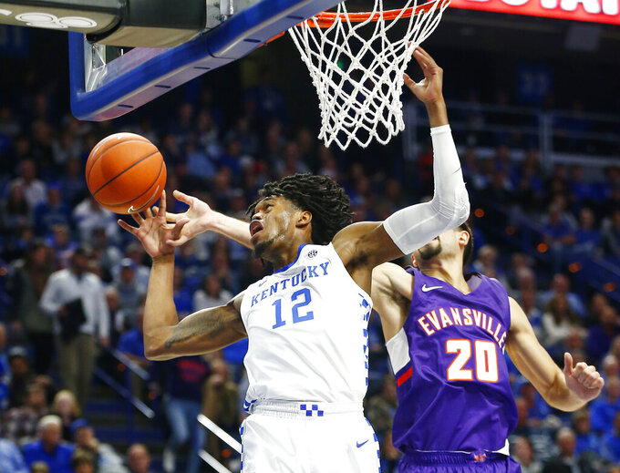 Kentucky's Keion Brooks Jr. (12) and Evansville's Sam Cunliffe (20) vie for a rebound during the first half of an NCAA college basketball game in Lexington, Ky., Tuesday, Nov. 12, 2019. (AP Photo/James Crisp)
