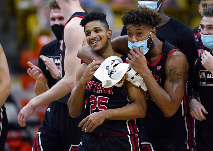 Utah guard Alfonso Plummer, left, is hugged by guard Jordan Kellier as time runs out in the second half of an NCAA college basketball game against Colorado, Saturday, Jan. 30, 2021, in Boulder, Colo. Utah won 77-74. (AP Photo/David Zalubowski)