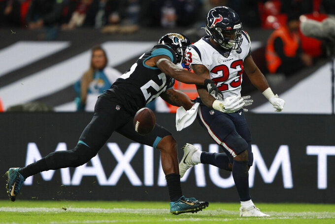 Houston Texans running back Carlos Hyde (23) loses the ball against Jacksonville Jaguars free safety Jarrod Wilson (26) during the second half of an NFL football game at Wembley Stadium, Sunday, Nov. 3, 2019, in London. (AP Photo/Ian Walton)