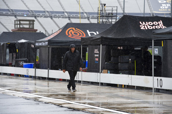 People walk in the pit area as rain falls before a NASCAR Cup series auto race at Dover International Speedway in Dover, Del., Sunday, May 5, 2019. (AP Photo/Jason Minto)