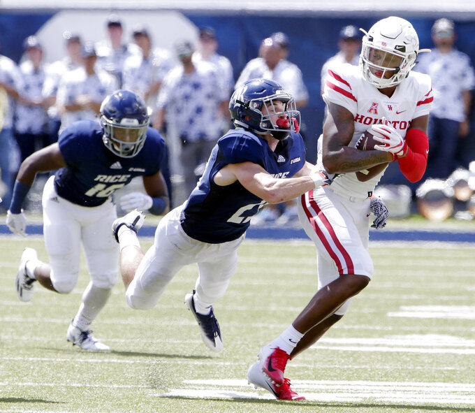 Houston wide receiver Keith Corbin, right, is caught by Rice safety Houston Robert (29), center, with defensive back Joshua Cummings (16), left, trailing during the first half of a NCAA college football game Saturday, Sep. 1, 2018, in Houston. (AP Photo/Michael Wyke)