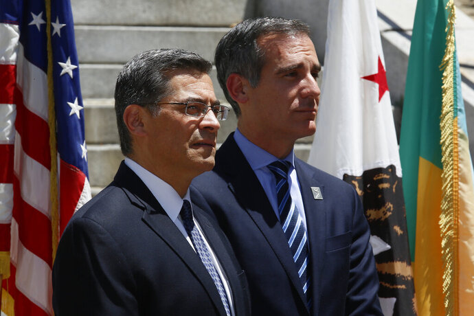 FILE - In this May 4, 2018, file photo, California Attorney General Xavier Becerra, at podium, announces at a news conference in Los Angeles that the city and county of Los Angeles, as well as four other cities have joined a lawsuit the state previously filed challenging the Trump administration's plan to ask people if they are U.S. citizens during the 2020 census. A U.S. judge in San Francisco will hear closing arguments Friday, Feb. 15, 2019, in a trial over the Trump administration's decision to add a citizenship question to the 2020 U.S. Census for the first time in 70 years. (AP Photo/Damian Dovarganes, File)