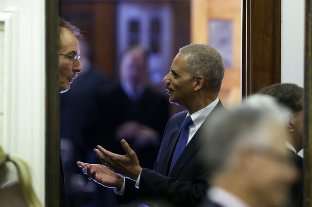 FILE - In this Nov. 13, 2012 file photo, Attorney General Eric Holder talks with U.S. District Judge Robert Pratt, left, in Des Moines, Iowa. Pratt, who has warned that systemic political corruption is a threat to U.S. democracy, is ridiculing President Trump's pardons, including those issued to convicted Republican campaign operatives and members of Congress.
