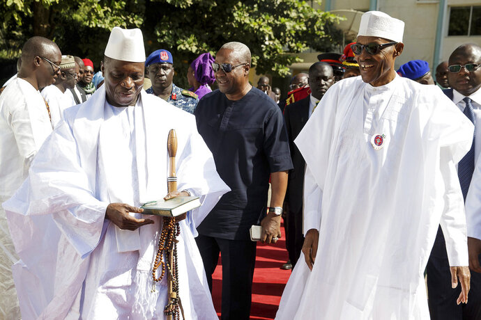 FILE - In this Friday Jan.13, 2017 file photo released by the Nigeria State House, Gambia President Yahya Jammeh, left, walks alongside with Nigeria President Muhammadu Buhari, upon arrival in Banjul Gambia. A survivor, families of the disappeared and human rights organizations are seeking the extradition and prosecution in Ghana of Gambia's former leader Yahya Jammeh for alleged direct involvement in the killing of more than 50 West African migrants in 2005. Human Rights Watch and TRIAL International are calling on Ghana's government to investigate new evidence they say ties Jammeh to the killings of Ghanaians, Nigerians and others. (Bayo Omoboriowo/Nigeria State House via AP, file)