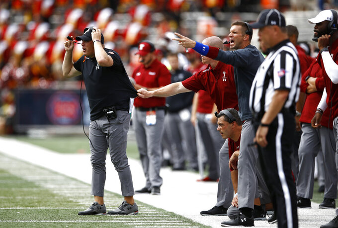 Temple head coach Geoff Collins, left, is pulled back toward the sideline as he directs players in the second half of an NCAA college football game against Maryland, Saturday, Sept. 15, 2018, in College Park, Md. (AP Photo/Patrick Semansky)