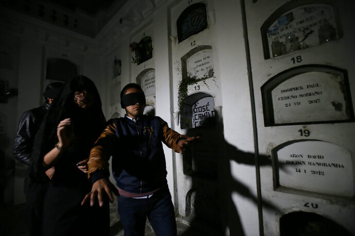 Blindfolded tourists walk through El Tejar cemetery, in downtown Quito, Ecuador, Wednesday, Sept. 11, 2019. They're there to get a taste of death while still alive, spending part of the night in a dark crypt at the El Tejar cemetery, the latest example of the so-called