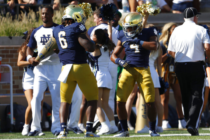 Notre Dame's Avery Davis (4) celebrates his 59-yard touchdown reception with Tony Jones Jr. (6) in the first half of an NCAA college football game against New Mexico in South Bend, Ind., Saturday, Sept. 14, 2019. (AP Photo/Paul Sancya)