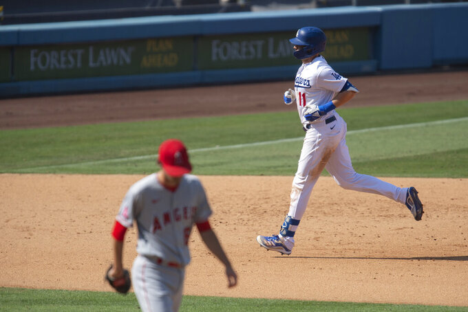 Los Angeles Dodgers' A.J. Pollock, right, rounds the bases after hitting a two-run home run during the seventh inning of a baseball game against the Los Angeles Angels in Los Angeles, Sunday, Sept. 27, 2020. (AP Photo/Kyusung Gong)