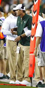 Colorado State head coach Mike Bobo, center, watches the first half of an NCAA college football game against Colorado, Friday, Aug. 31, 2018, in Denver. Bobo, who has been hospitalized with peripheral neuropathy, coached last Saturday's game against Hawaii from the press box. (AP Photo/David Zalubowski)