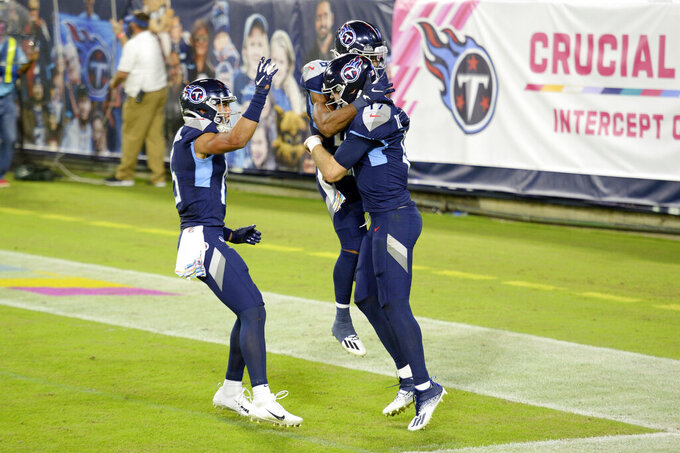 Tennessee Titans quarterback Ryan Tannehill (17) is congratulated after scoring a touchdown on a 10-yard run against the Buffalo Bills in the first half of an NFL football game Tuesday, Oct. 13, 2020, in Nashville, Tenn. (AP Photo/Mark Zaleski)